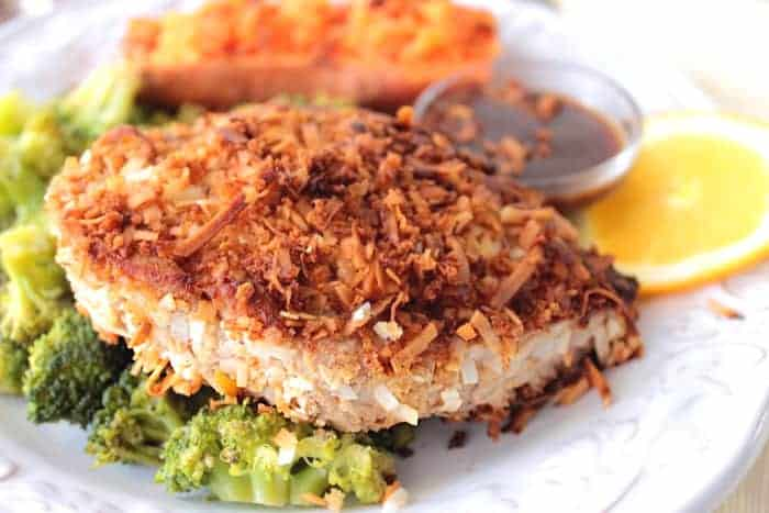 A Coconut Crusted Tuna Steak on a white plate with broccoli and a sweet potato.
