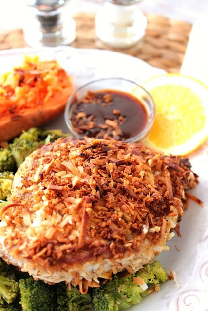 Colorful vertical image of a tuna steak crusted with coconut, a dipping sauce, sweet potato and broccoli.