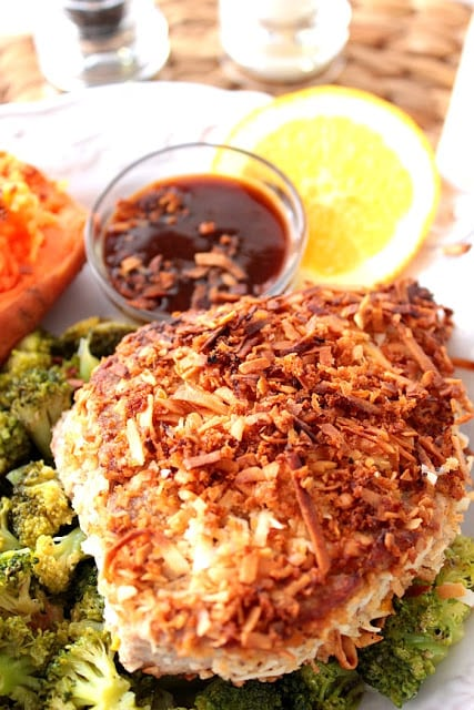 Vertical photo of browned coconut crusted tuna steak with an orange slice, dipping sauce, and broccoli on a white plate.