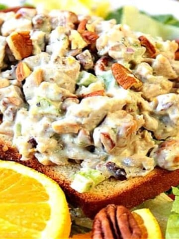 A slice of bread topped with orange cashew chicken salad with pecans and fresh oranges and lettuce.