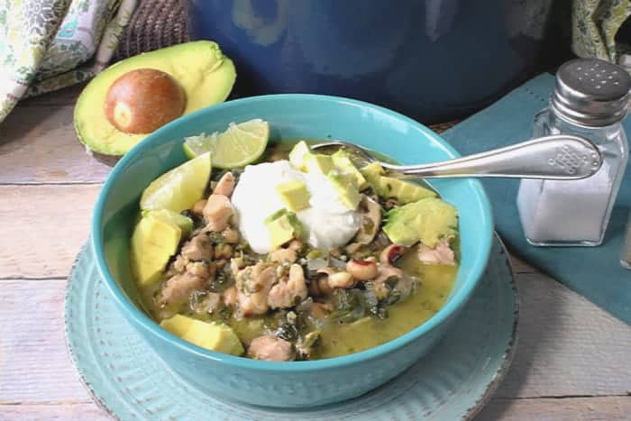 A bowl of black-eyed pea chicken chili with avocado and sour cream.