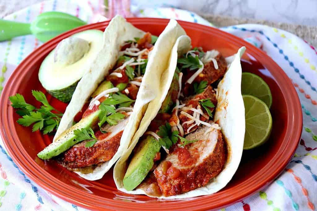 Lime Marinated Pork Tacos on an orange plate with limes. - kudoskitchenbyrenee.com