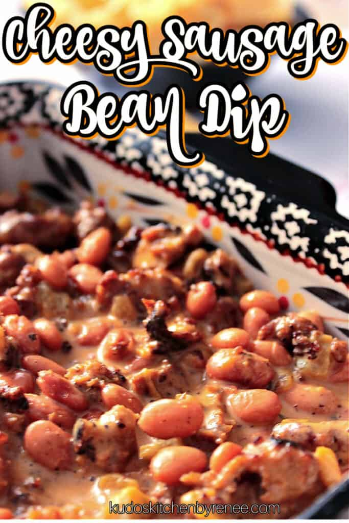 A vertical closeup photo along with a title text graphic of Cheesy Sausage Bean Dip in a square casserole dish.