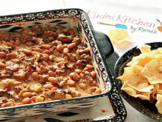 An offset horizontal photo of Cheesy Sausage Bean Dip in a square casserole dish and a bowl of nacho chips on the side.