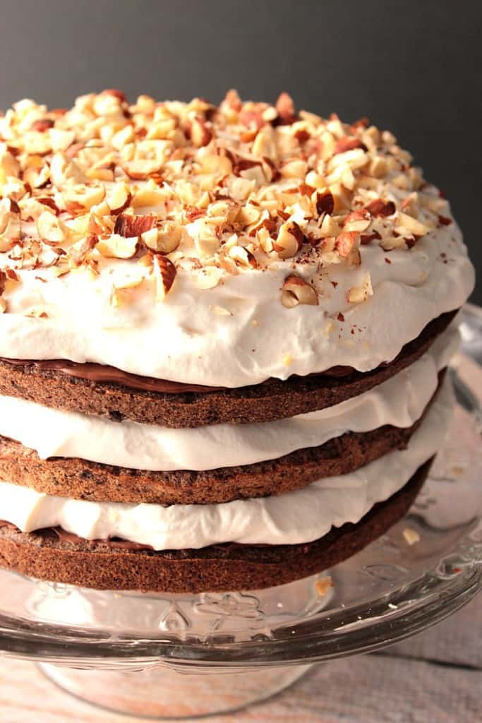 Chopped Hazelnuts top a chocolate cake with whipped cream.