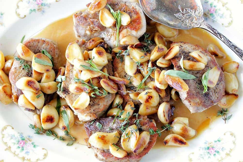 Garlic Lovers Pork Chops on a platter with garlic and herbs. - kudoskitchenbyrenee.com