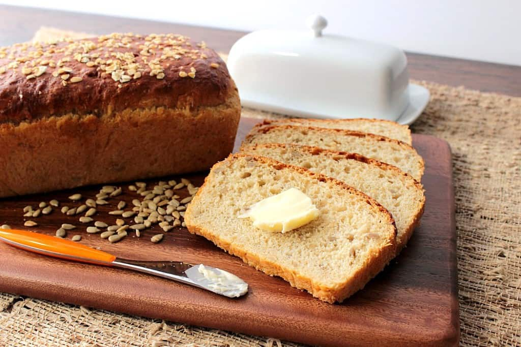 A horizontal photo of Oatmeal Honey Bread with Sunflowers along with a pat of butter and a butter dish.