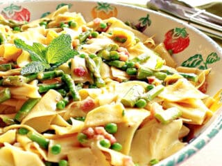An offset photo of a flat bowl filled with Pappardelle with Spring Vegetables of asparagus and peas.