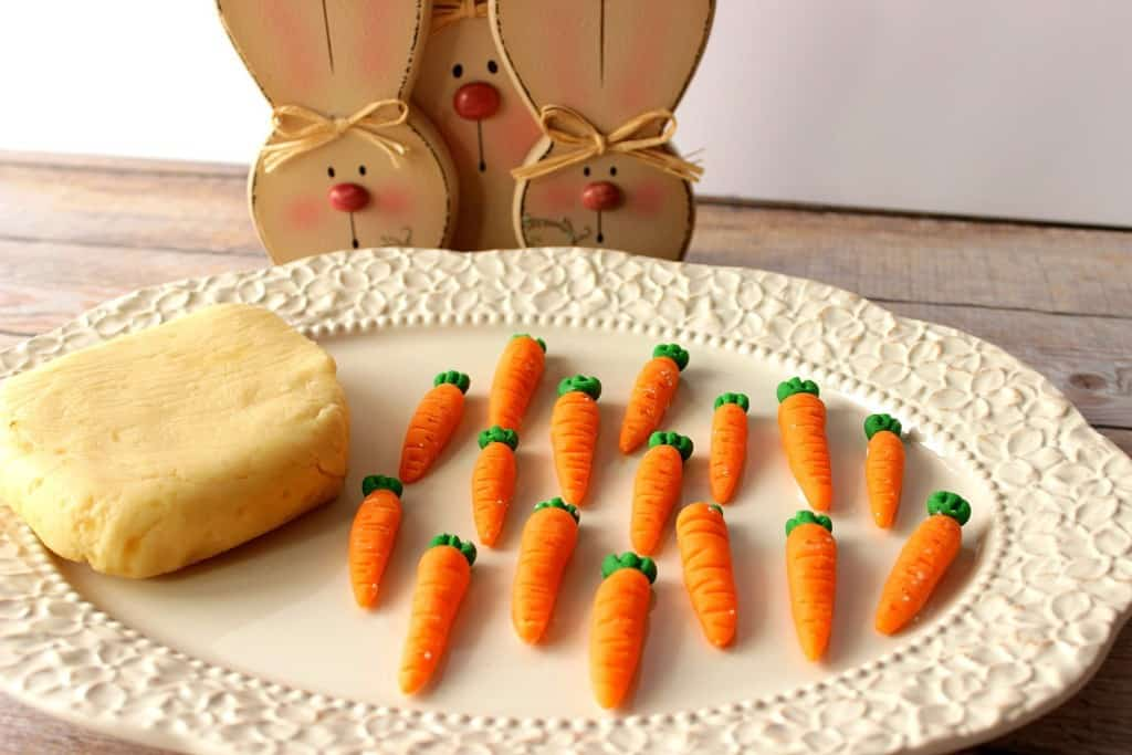 A white platter with a block of homemade marzipan and marzipan carrots, with bunnies in the background.