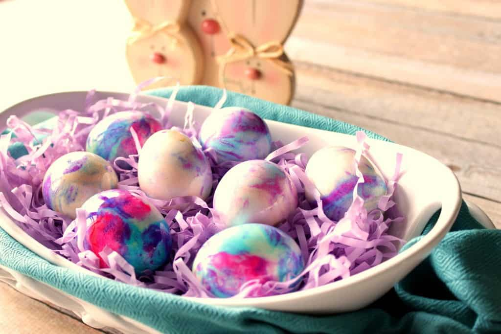 Mayonnaise Tie Dyed Easter Eggs in a white bowl and a blue napkin.