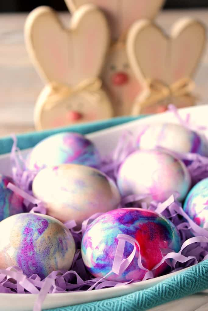 Closeup photo of pastel marbleized Easter eggs with bunny decorations in the background.