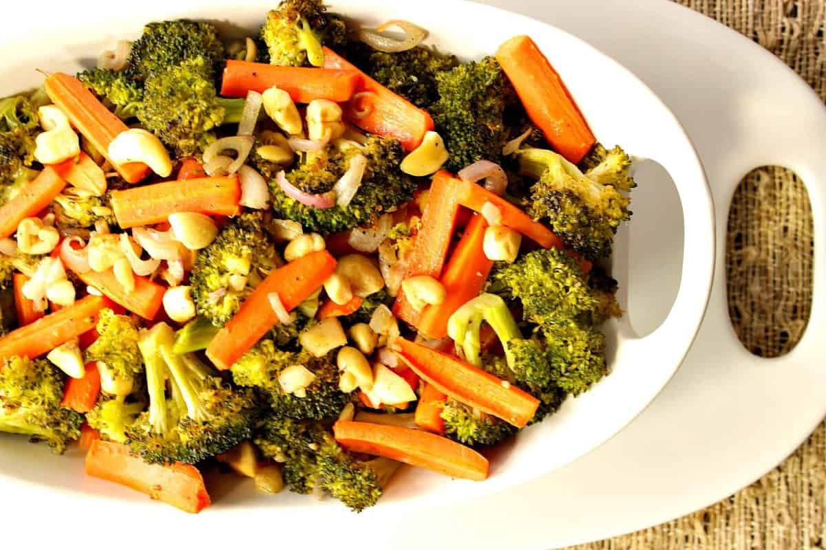 Oven Roasted Carrots, Broccoli, Shallots and Cashews in a white oval bowl with a white oval platter underneath