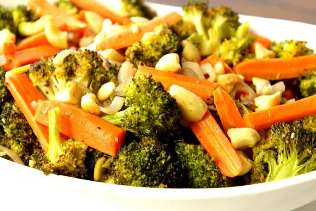 Closeup photo of chopped broccoli, carrots, and cashews in a white bowl.