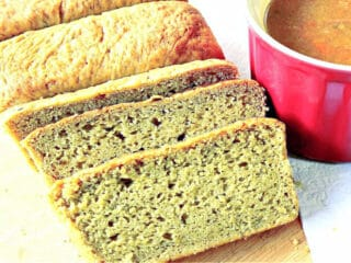 A sliced loaf of Avocado Yeast Bread along with a red mug of soup on the side.