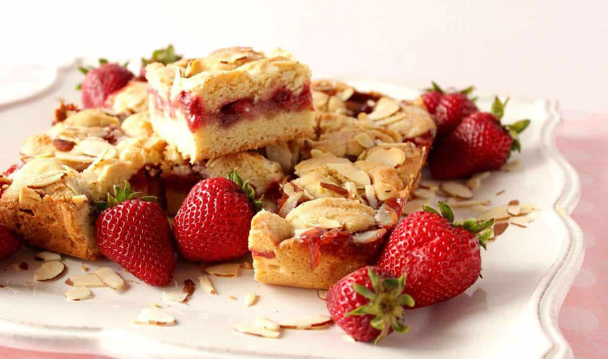 A bunch of strawberry cobbler bars on a white scalloped plate with fresh strawberries as garnish.