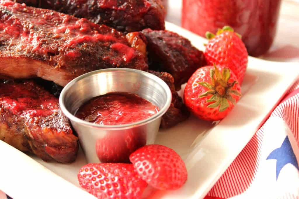 A closeup horizontal photo of a small dish of strawberry bbq sauce with ribs on a white plate and fresh strawberries.
