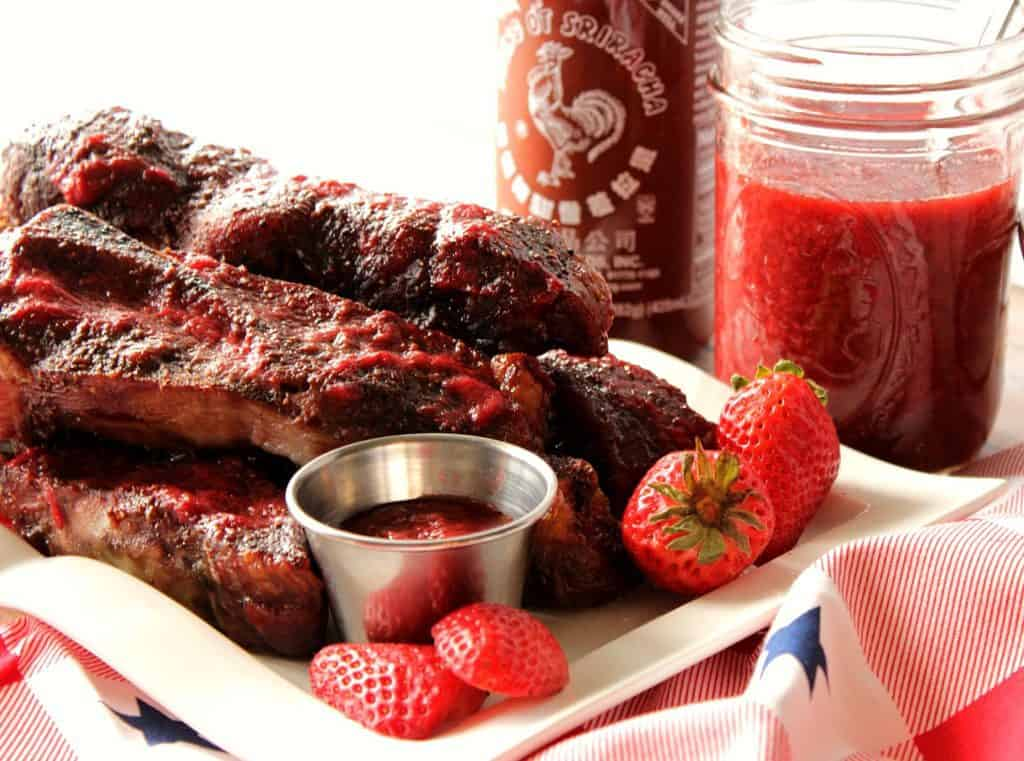 Pile of pork ribs on a white plate the strawberries and bbq sauce.