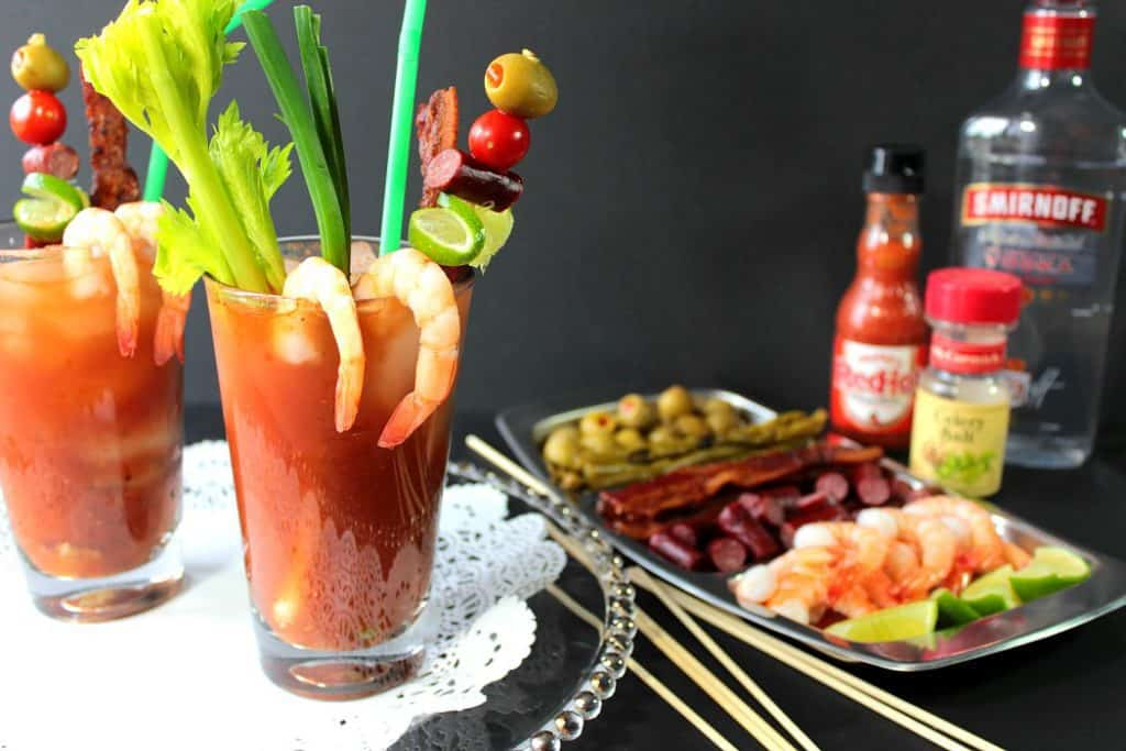 2 bloody Mary drinks on a tray with a doily, loaded with shrimp, celery, olives, and straws.