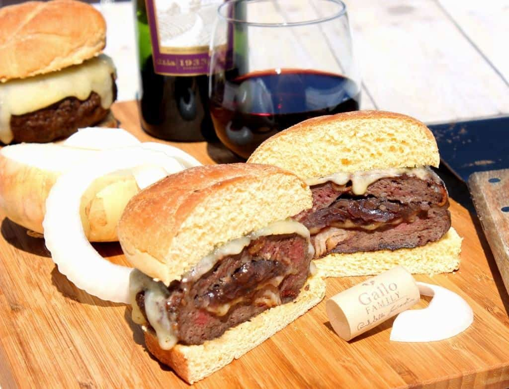 Burgers Stuffed with Caramelized Onions on a cutting board with a glass of red wine in the background.