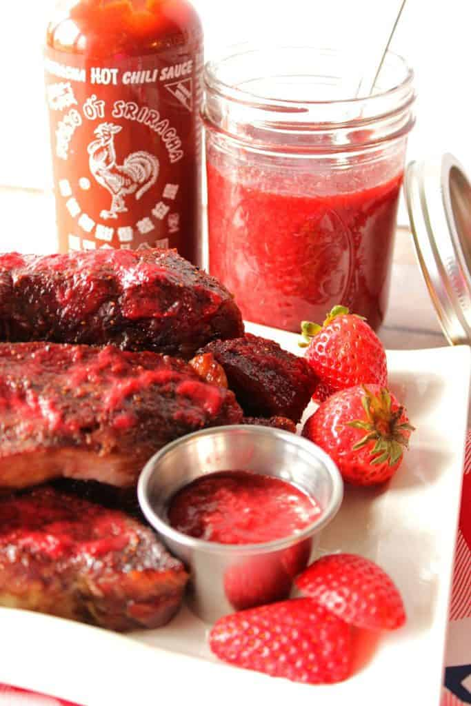A vertical image of ribs on a plate with strawberry sriracha bbq sauce in a small cup and in a jar in the background.