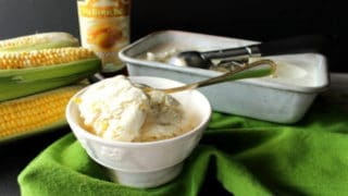 A small white bowl filled with no-churn roasted sweet corn ice cream in the foreground with ears of corn and a loaf pan filled with ice cream in the background.