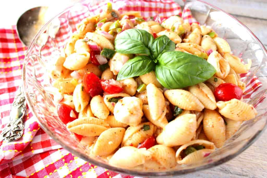 Pasta salad in a glass bowl with a red and white checked napkin, a large spoon, and fresh basil leaves.
