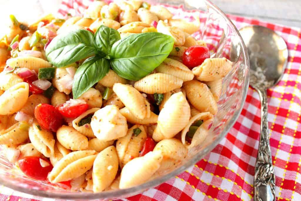 Large glass bowl filled with shell pasta salad, grape tomatoes and fresh basil leaves.