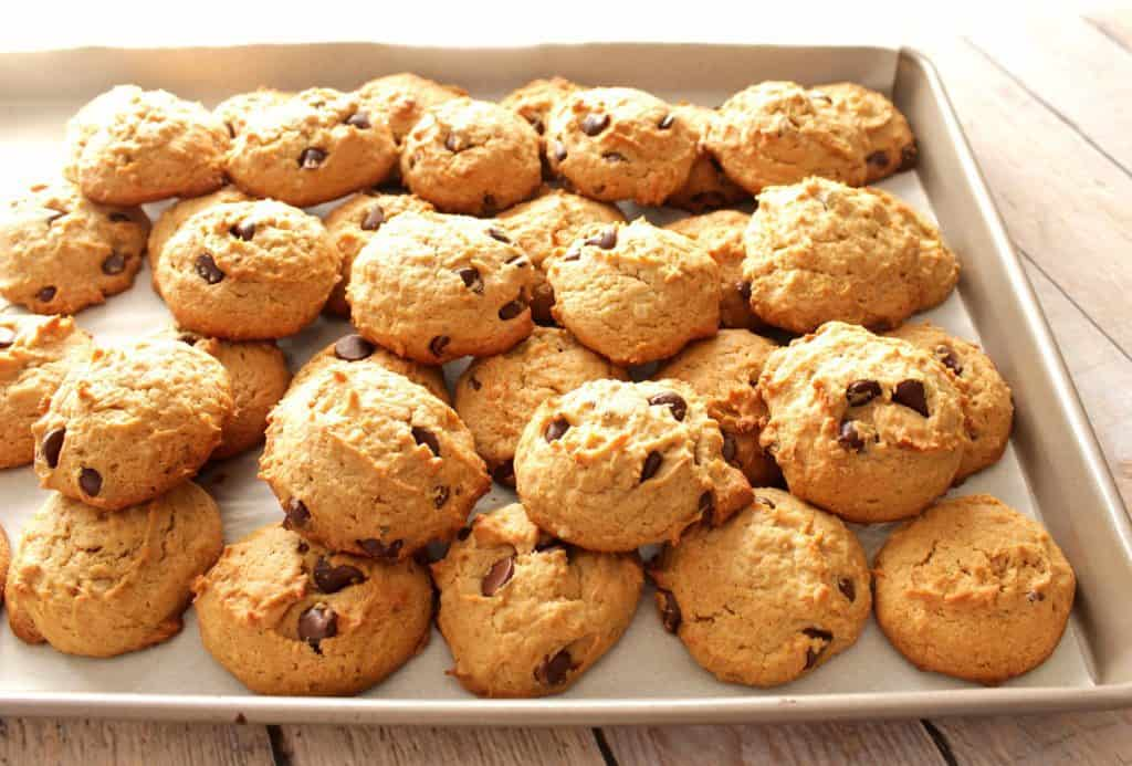 A horizontal photo of a baking sheet piled high with peanut butter chocolate chip banana cookies.