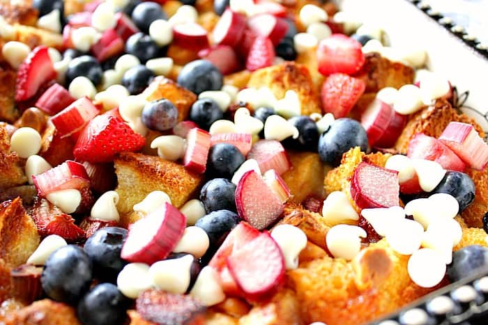 Closeup photo of bread pudding with rhubarb, strawberries, blueberries and white chocolate chips.