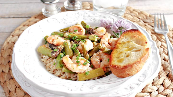 A pretty white bowl filled with Shrimp and Asparagus along with brown rice and a piece of garlic bread.