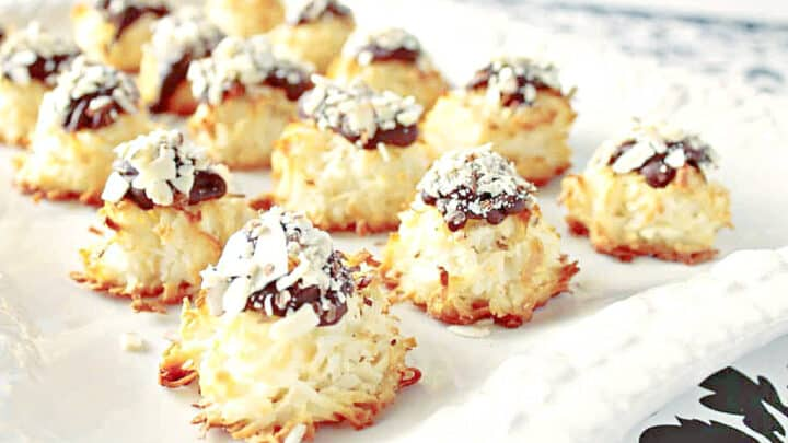 A white tray filled with Almond Joy Coconut Macaroons with chocolate and almonds on top.