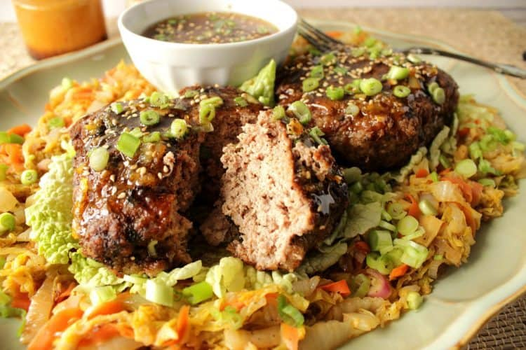A plate of crispy duck patties with Asian cabbage and orange dipping sauce.