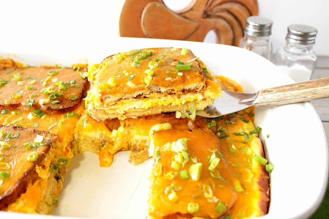 A slice of egg sandwich breakfast casserole on a spatula and a white baking dish