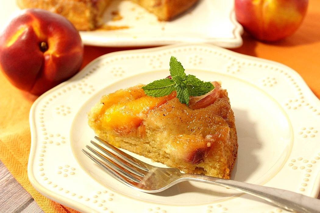 Slice of nectarine upside down cake on a white plate with a sprig of mint and a fork