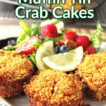 muffin tin crab cakes on a white plate with a salad and lemon wedges in the background.