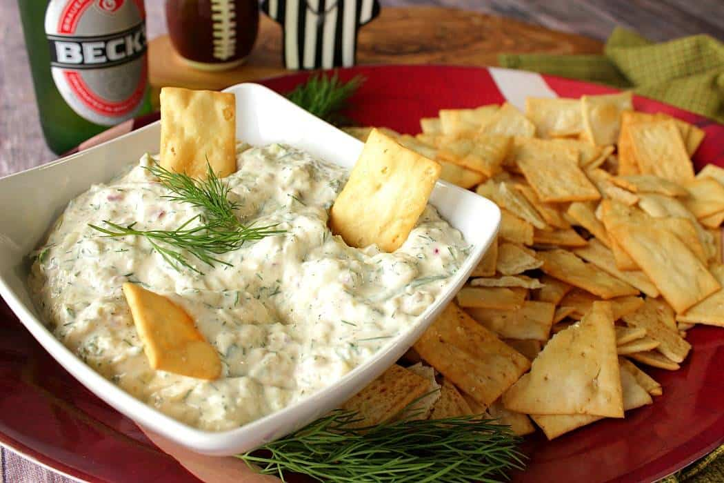 Cucumber dill dip in a bowl with crackers on the side and fresh dill sprig in the center.