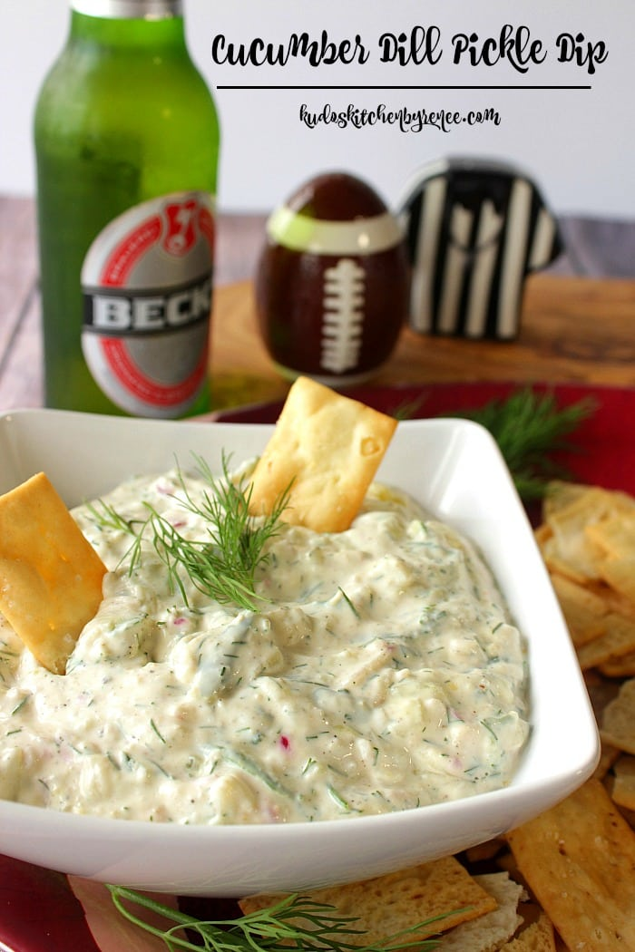 Closeup photo of cucumber dill dip with crackers and fresh dill in a square white bowl.