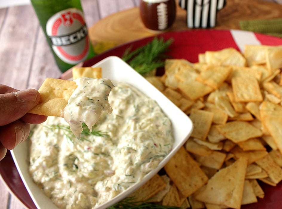 A cracker with Cucumber Dill Pickle Dip along with a bottle of beer in the background and crackers on a platter.
