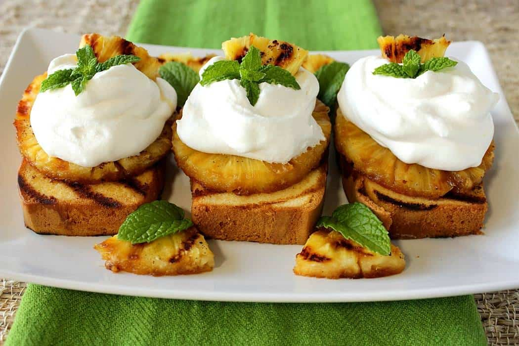 Three slices of grilled pineapple pound cake on a plate with whipped cream and mint.