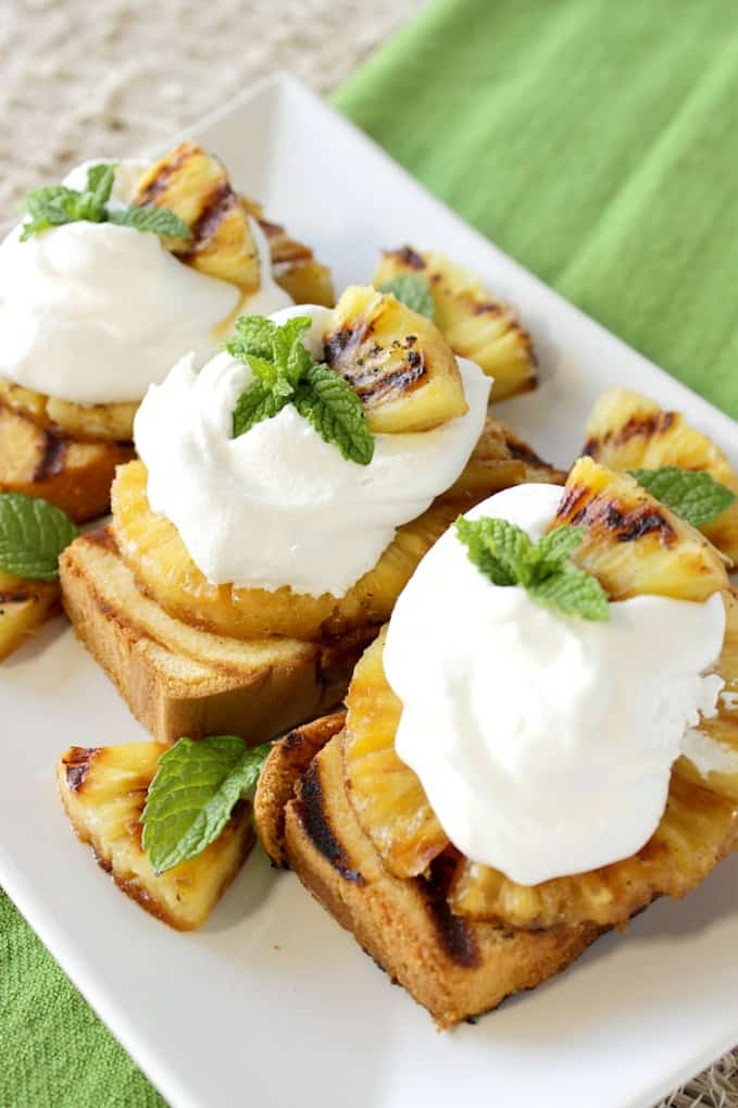 Vertical photo of grilled pound cake with pineapple slices on top along with whipped cream and mint.