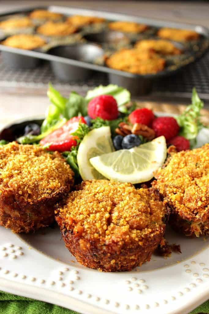 Meaty Cornflake Muffin Tip Crab Cakes on a white plate with a salad and a muffin tin in the background.