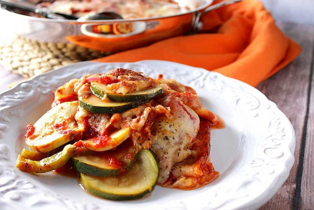 Italian Zucchini Parmesan on a white plate with a skillet and orange napkin in the background.