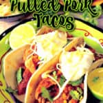 Closeup vertical image of two slow cooker pulled pork tacos in a green bowl with sour cream, cilantro, and shredded cheese.