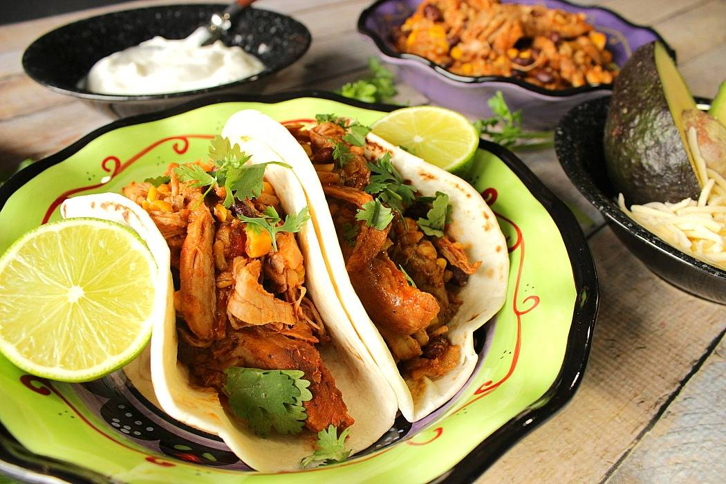 Slow Cooker Shredded Pork Tacos in a green and black bowl with lime wedges and cilantro.