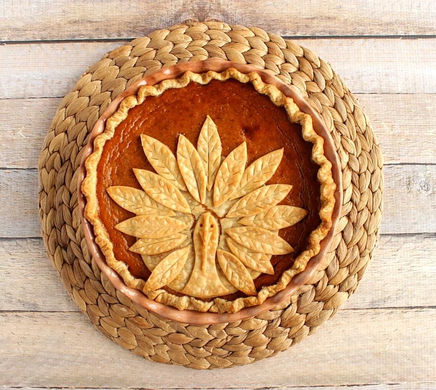 Overhead photo of an entire turkey crust pumpkin pie on a woven place mat.