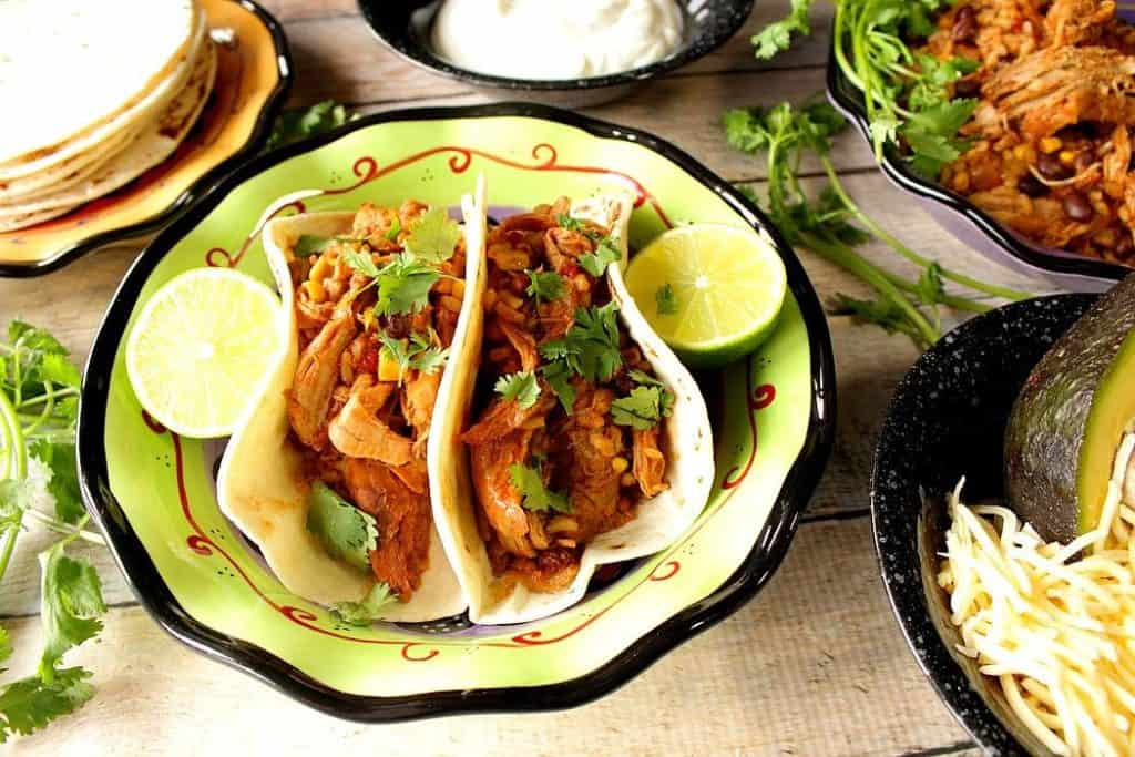 pulled pork tacos on a plate with lime wedges and fresh cilantro