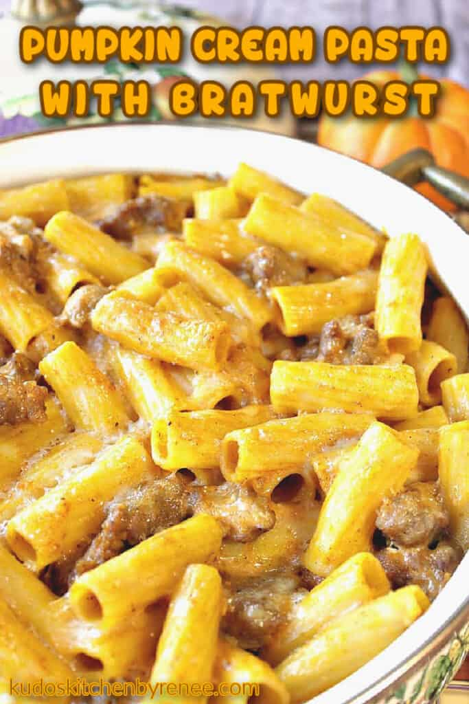 A vertical closeup photo of pumpkin cream pasta with bratwurst in a casserole dish and a title text overlay graphic