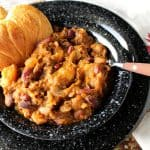 A bowl of butternut squash chili with a pumpkin shaped biscuit.
