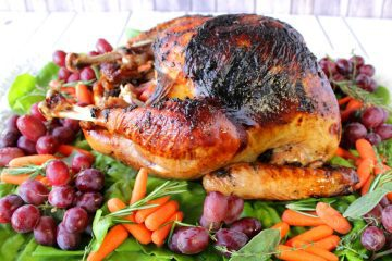 A beautifully browned roasted turkey on a platter with grapes, carrots, and greens.