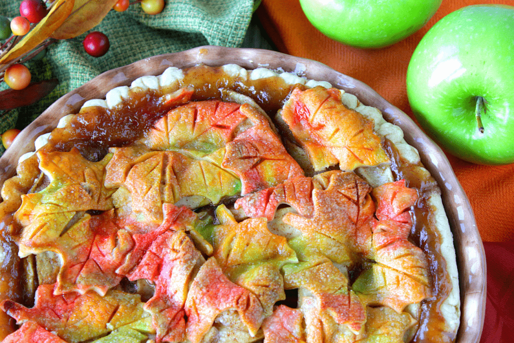 Overhead photo of an autumn leaves apple pie in a pie dish with apples.